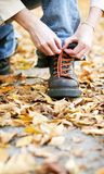 Shoe in fall. Woman sitting down and tieing her shoe Stock Images