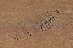 Shoe footprint on wet sand texture Royalty Free Stock Photo