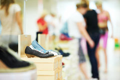 Shoe in footwear store. Pair of female shoes standing in footwear shop with blurred peoples on background royalty free stock photos