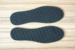 Shoe insoles on the wooden background. New shoe insoles on the wooden background stock photos