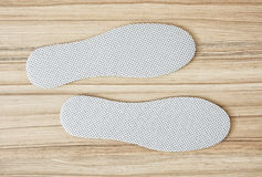 Shoe insoles on the wooden background. New white shoe insoles on the wooden background stock photos
