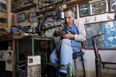 Shoe maker. Shoe repaire old man inside his workshop stock photo