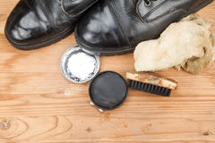 Shoe polish with brush, cloth and worn boots on wooden platform Stock Photos