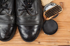 Shoe polish with brush, cloth and worn boots on wooden platform Royalty Free Stock Photos