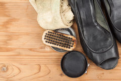 Shoe polish with brush, cloth and worn ladies court shoe on wood Stock Photography