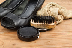 Shoe polish with brush, cloth and worn ladies court shoe on wood Royalty Free Stock Photos