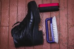 Shoe Polishing with female legs in black boots royalty free stock image