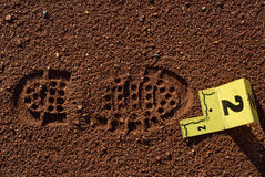 Shoe Print Evidence. Shoe impression in dirt with yellow numbered placard marking evidence at crime scene Royalty Free Stock Photography