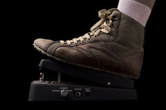 Shoe pushing down a black wah wah guitar pedal Royalty Free Stock Photography