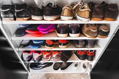 Shoe rack man sneakers. Shoe rack for man many sneakers shelves royalty free stock photos