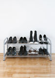 Shoe rack on a wooden floor. Shoe rack with black shoes and boots, on a wooden floor, besides a white wall royalty free stock photos