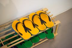 Shoe Rack with yellow and green rubber sandal or slippers. Shoe Rack with yellow and green rubber sandal or slippers stock photography