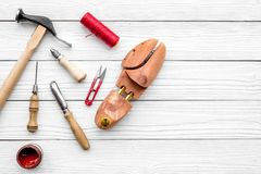 Shoe repair. Wooden last, hammer, awl, knife, thread on white wooden background top view copyspace Royalty Free Stock Images
