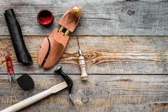 Shoe repair. Wooden last, hammer, awl, knife, thread on wooden background top view copyspace. Shoe repair. Wooden last, hammer, awl, knife, thread on wooden royalty free stock photo
