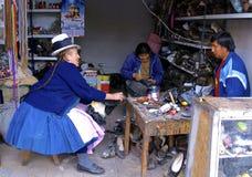 Shoe repairman. Native quechua woman. Peru Royalty Free Stock Photo