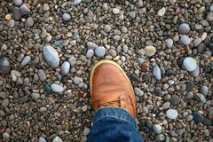 The foot on the rocks. male leg on the rocks. The shoe on the rocks. male leg on the rocks. Travel, walking Royalty Free Stock Photography