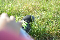 Shoe's grass kid leg feeds trainers. Green Royalty Free Stock Photo