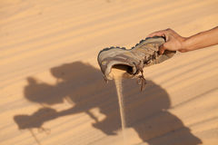 Shoe with sand. Female hand pouring white sand left from her shoe in Muine desert Stock Photos