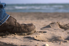 Shoe on a sandy beach. Walking the beach on a sunny day. Direct sunlight glows around the leg. Good to show healthy living and/or vacation Royalty Free Stock Photos