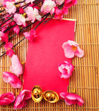 Shoe-shaped gold ingot (Yuan Bao) and Plum Flowers with red packet Stock Images
