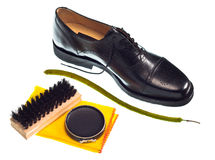 Shoe Shine. Concept with shiny black men's shoe, black polish, brush and yellow duster Stock Photo