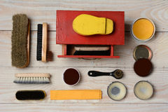 Shoe Shine Kit. High angle view of  an antique shoe shine kit and its accessories, including brushes, polish, and buffing cloth. Horizontal format on a white Royalty Free Stock Images