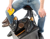 Shoe shiner in front of his equipment Stock Photos