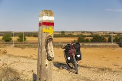 Shoe sole and a yellow arrow on a signpost and a bicycle. A shoe sole and a yellow arrow on a signpost and a bicycle equipped with rear pannier bags for Bicycle stock photos