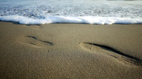 Shoe Step and Waves. Shoe step mark on sand beach with waves background at Wetar Island, Maluku, Indonesia stock image