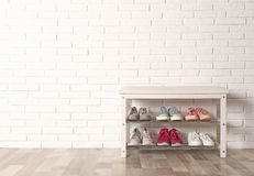 Shoe storage bench with different sneakers near wall, space for text. Shoe storage bench with different sneakers near brick wall, space for text royalty free stock images