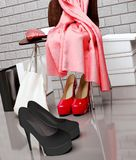 At the shoe store. Close-up of the chair, red scarf,  bag. At the shoe store. Close-up of the chair, red scarf,  bag and  shopping bags  shoes lying on the Stock Photo