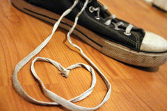 Shoe String Hearts and Sneakers. Sneaker with shoe laces in the form of a heart. Old and worn out blue shoe Royalty Free Stock Photography