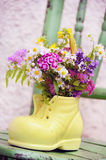 Shoe vase with colorful forest flowers Stock Images