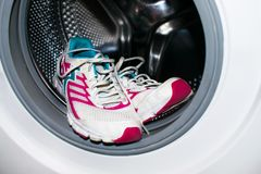 Shoe washing. White and pink sneakers wash in the washer (automa stock images