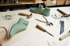 Shoemaking supplies. Shoe workpieces and handtools of cobbler on table of shoemaker royalty free stock image