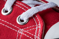 Shoelace eyelet. Red canvas shoe with white laces focused on the eyelet stock photography