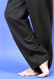 Shoeless. A man in black slacks standing barefoot with his legs on crossed over the other Stock Images