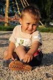 Shoeless child sitting on playground. Portrait of a shoeless child, a little boy, sitting on the ground on a playground stock photos