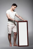 Shoeless Mann, der weißes Brett mit leerem Badekurort anzeigt Lizenzfreies Stockbild