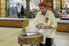 Shoemaker artisan in national clothes in the pavilion of Turkey. DUBAI, UAE - DECEMBER 4, 2017: Shoemaker artisan in national clothes in the pavilion of Turkey stock photo
