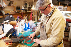 Shoemaker cutting and gluing leather in a workshop Royalty Free Stock Photo