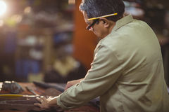 Shoemaker cutting a piece of leather Stock Photography
