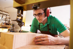Shoemaker cutting and shaping wood to make shoe lasts Royalty Free Stock Images