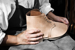 Shoemaker. Detail of the hands of a Shoemaker, manufacturing boots royalty free stock photo