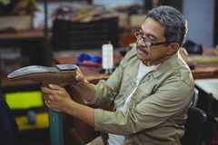 Shoemaker examining a shoe. In workshop Royalty Free Stock Images