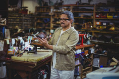 Shoemaker examining a shoe. In workshop Stock Photos