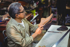 Shoemaker examining a shoe. In workshop Stock Images