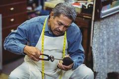 Shoemaker hammering on a shoe. In workshop Stock Images