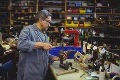 Shoemaker hammering on a shoe. In workshop Stock Image