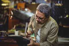 Shoemaker hammering on a shoe. In workshop Royalty Free Stock Photo